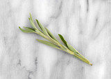 Top view of an organic sage branch atop a gray marble cutting board. - 186906403