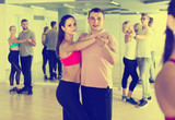 men and women  of different ages dancing salsa in dance hall - 186906658