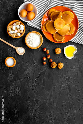 Foto Murales Make fluffy pancakes. Ingredients, cakes and toppings like nuts and honey on black background top view copyspace
