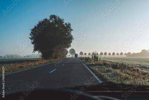 Highway in rural misty landscape at sunrise. Driver's view.