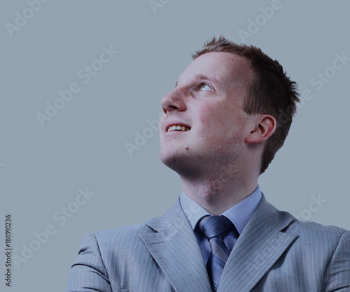 Closeup portrait of pensive handsome smiling man looking up in s