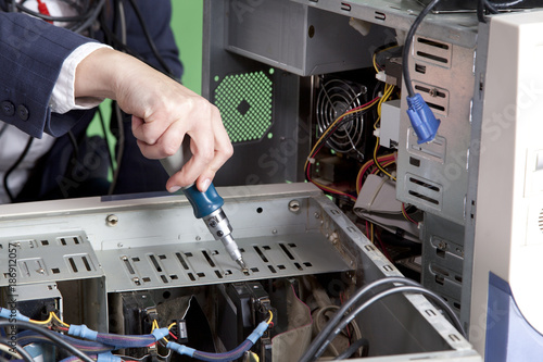 Female hands with screwdriver and disassembled system unit