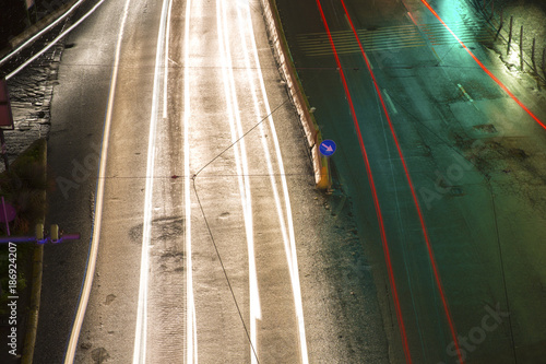 Papiers peints Autoroute nuit Detail of car traffic in a street of an Italian city. White and red headlights leave a trail due to long exposure. In the background the port of Naples, Italy.