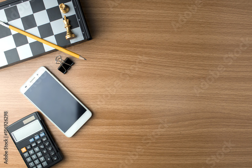 smartphone with office object on wood table
