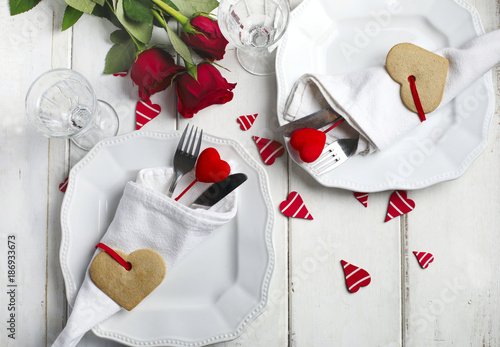Festive table setting for Valentine's Day with cutlery and gift boxes on white wooden table - 186933673
