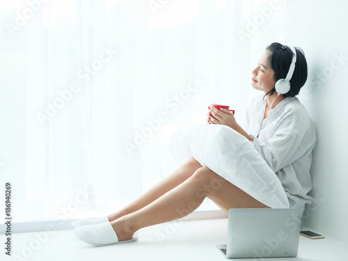 Asian woman drinking coffee in living room and listen music - 186940269