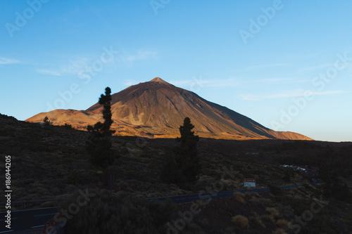 Deurstickers Canarische Eilanden Orange sunrise light on volcano in desert landscape