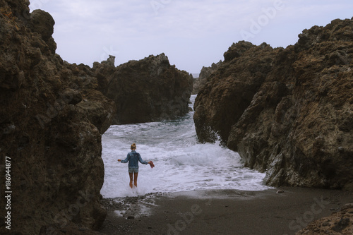 Papiers peints Iles Canaries Girl standing on sand beach playing with waves in cloudy weather