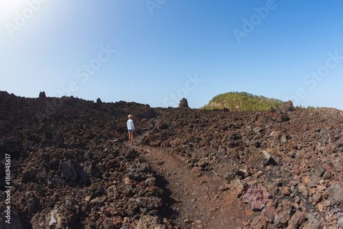Foto op Plexiglas Cappuccino Girl walking in dark volcanic landscape with green trees