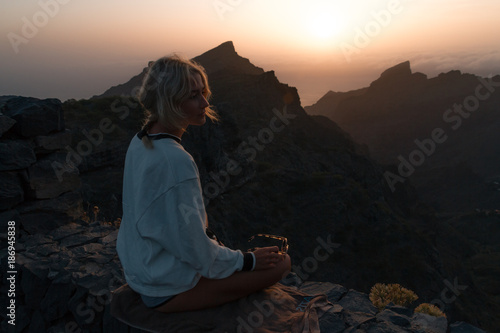 Poster Canarische Eilanden Young blond woman in shorts looking at rocky landscape with steep cliffs while sunset