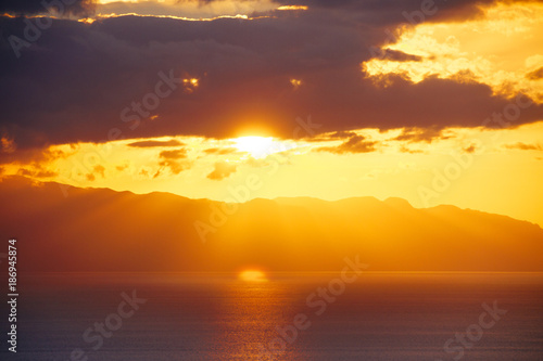 Foto op Canvas Canarische Eilanden Sunset light behind clouds above mountains and ocean