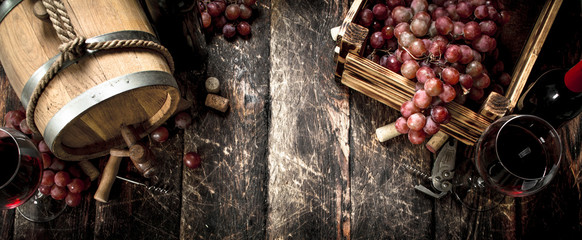 Wine background. A barrel with red wine and freshly grapes.