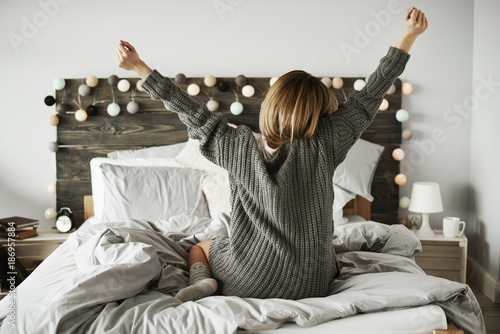 Rear view of woman stretching in her bed - 186957884