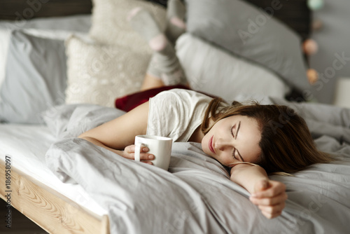 Woman with coffee reclining in bed - 186958097