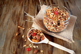 Granola in a glass jar and wooden spoon. Healthy nutrition concept. Rustic style - 186964425