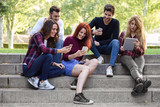 Young people using smartphone and tablet computers outdoors - 186979454