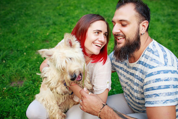 Portrait of happy young adult couple with dog
