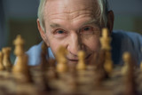 Senior confident man looks at the chess board - 186984002