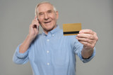 Senior man making a phone call and holding credit card isolated on gray background - 186984087