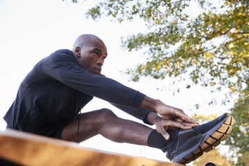 Young black man stretching leg on a bench in park, close up