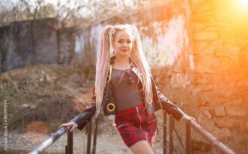 Deurstickers Kapsalon A girl with dreadlocks in a leather jacket and a short skirt stands against the background of an old stone wall in the rays of a bright sun