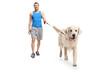 Young man in sportswear walking a dog