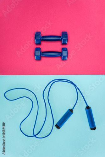 Sports dumbbells and skipping rope isolated on pink and blue - 186994819