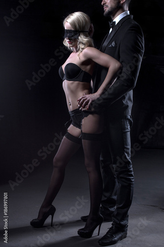 Stylish man touching sexy blonde lover in blindfold