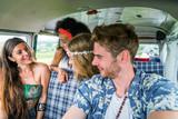 Happy friends driving a vintage minivan - 187004007