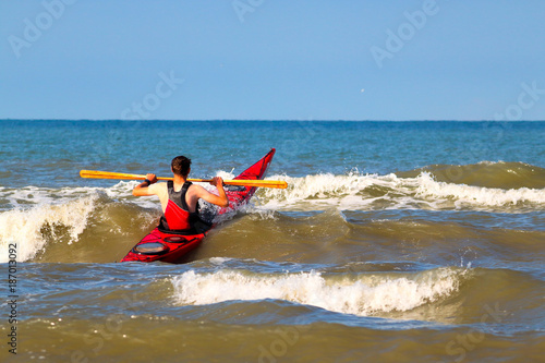 Man on a sea red kayak is paddling at the wave in Black sea