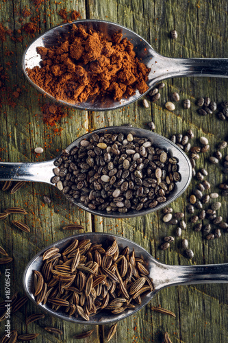Spoons of cumin, cayenne peppers and chia seeds on a wooden background - 187015471