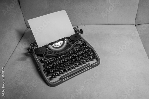 Typewriter ready for use with blank paper installed macro black and white background. Top view