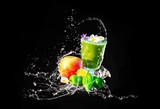 Grüner Smoothie mit essbaren Blüten und Früchten, Wasserspritzer, isoliert auf schwarz