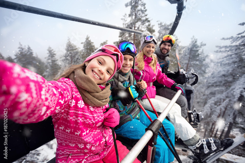 Happy family in cable car climb to ski terrain - 187020425