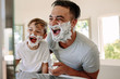 Leinwandbild Motiv Father and son having fun while shaving in bathroom
