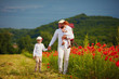 father and sons walking through the poppy flower field at summer day