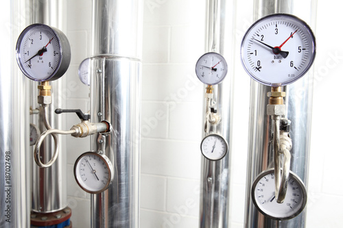 manometer, pipes and faucet valves of heating system in a boiler room