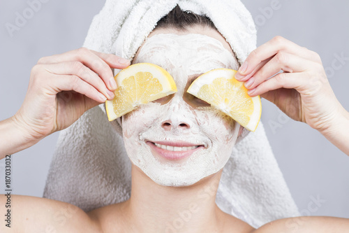 beauty woman getting facial mask. Attractive young woman with fruit mask on face at spa salon.