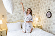 Young beautiful woman throwing white pillow at camera and starts a pillow fight.