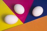 Easter eggs on a multicolored background of yellow, blue, pink and orange
