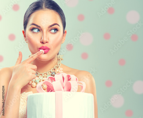 Funny joyful beauty model girl holding big beautiful party or birthday cake over green background and tasting it - 187056204
