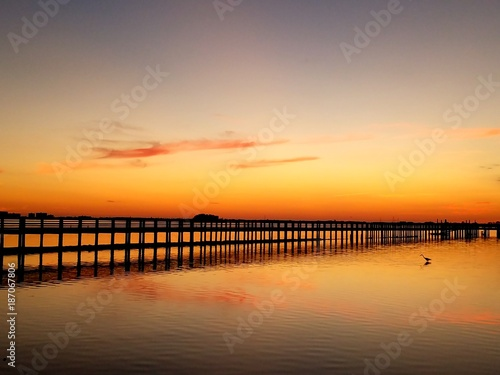 Foto op Canvas Zee zonsondergang Golden sunset over a fishing pier jetty with water reflection