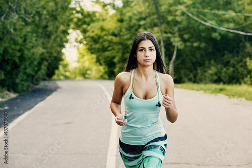 Fototapeta A young woman is Jogging in a city Park