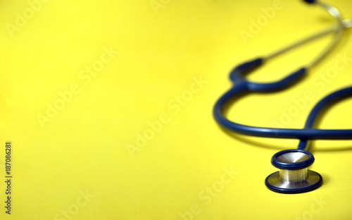Leinwanddruck Bild Blue stethoscope on yellow background. For check heart or health check up concept
