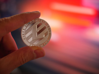 Hand holding silver litecoin LTC coin on colorful background, closeup.