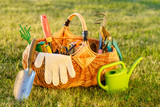 Gardening tools in basket and watering can on grass - 187091497