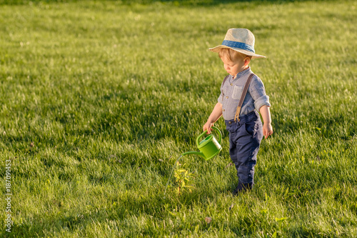Toddler child outdoors. One year old baby boy wearing straw hat using watering can - 187091453