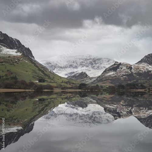 Deurstickers Grijs Beautiful Winter landscape image of Llyn Nantlle in Snowdonia National Park with snow capped mountains in background