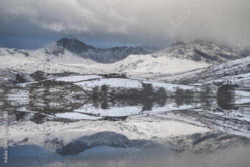 Beautiful Winter landscape image of Llynnau Mymbyr in Snowdonia National Park with snow capped mountains in background