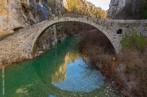 Foto Murales Kokori's old one-arch stone bridge (Noutsos) situated on the river of Voidomatis in the municipality of Central Zagori, near the village of Koukouli. It was constructed in 1750 AD